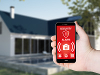 Hand hold a phone with security alarm app on a screen on the background of a house. All screen graphics are made up.