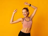 Slim Young Lady In Fitwear Dancing On Yellow Studio Background. Empty Space